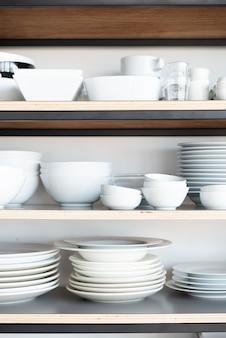 Посуда белого цвета на полке