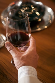 テーブルの上の赤ワインのガラスを持っている手
