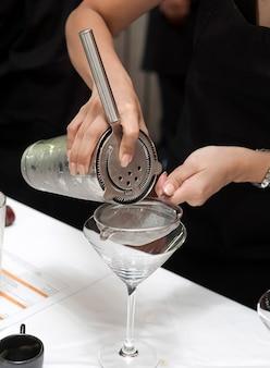 Руки наливая коктейль на стол