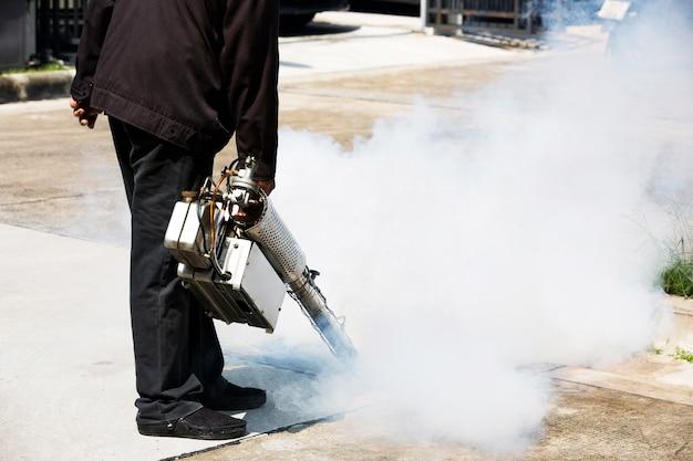 害虫駆除のためのマンホールにスモークマシンで作業する人