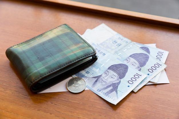 木製のテーブルに緑の財布と韓国のお金