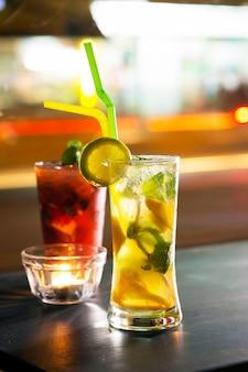 Два стакана фруктового мохито подают на стол
