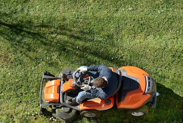 乗用草刈り機で芝生を刈る男