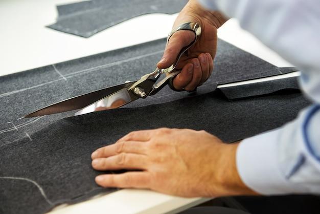 Портной раскрой ткани большими ножницами