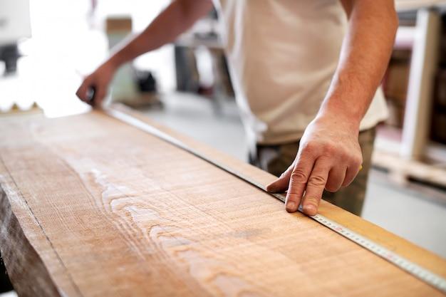 Плотник с помощью измерительной ленты