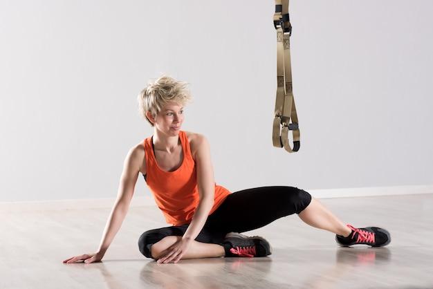 Женщина сидит возле тренировочных колец в воздухе