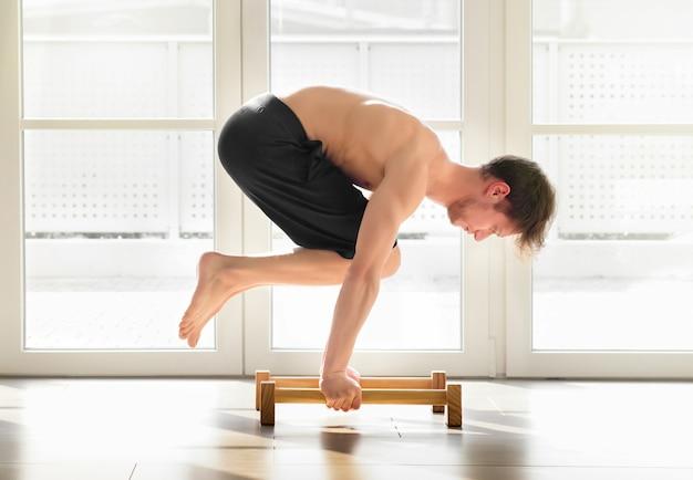 Молодой человек делает позу воронки по художественной гимнастике