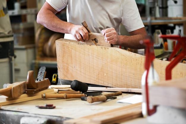 Плотник строгает блок дерева в мастерской