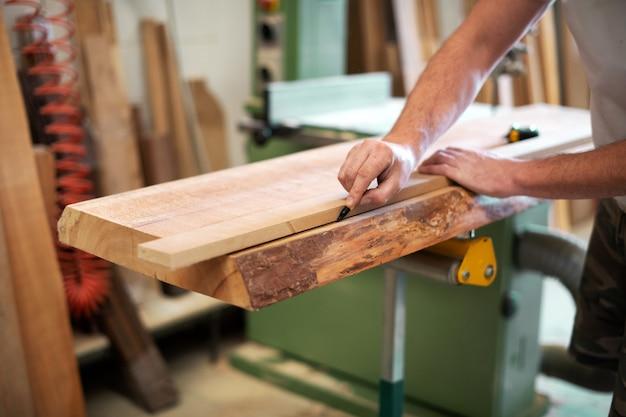 Плотник или столяр, измеряющий кусок дерева