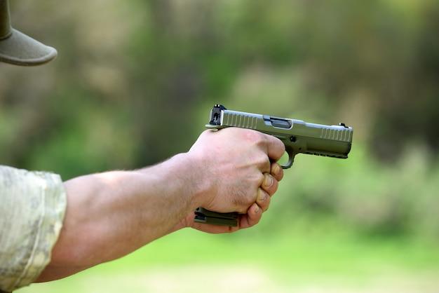 Солдат прицеливается из автоматического пистолета