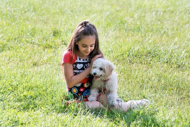 ペットのプードルをなでる愛する少女