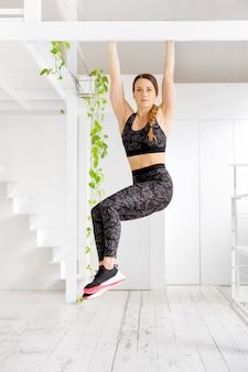 Молодая женщина атлетической пригонки разрабатывая делающ пальцы ноги для того чтобы запереть тренировку в спортзале светлого тонового изображения с зелеными растениями