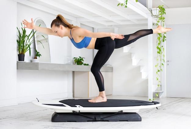 腕を伸ばして片足でバランスをとるサーフィンヨガランナーポーズを行う若い女性