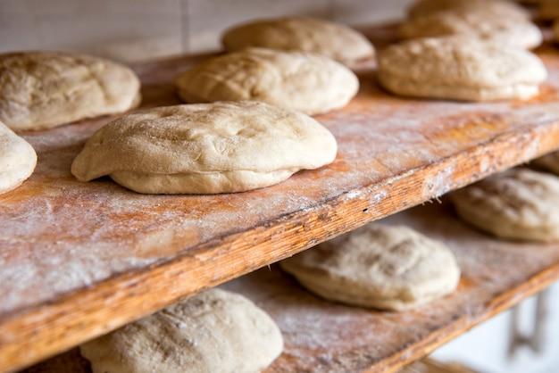 パン屋のオーブンに入る準備ができている木製の棚のパンに形を整えた生のパン生地