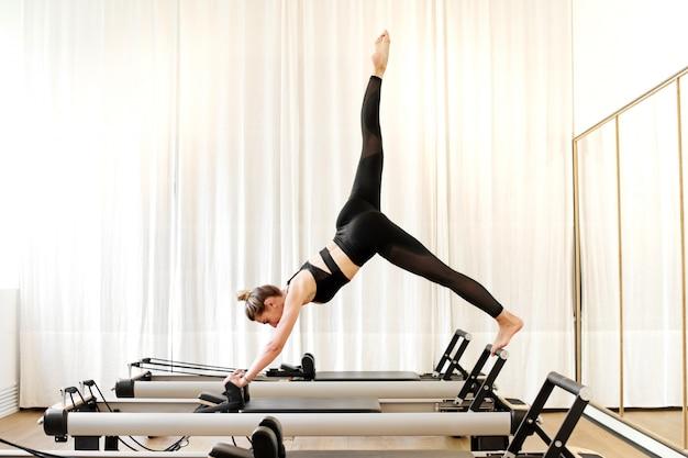 Женщина делает упражнения йоги щука одной ноги