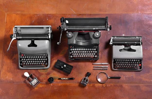 木製の机の上のタイプライター、スタンプ、ペン