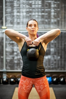 ケトルベルの重量を保持している若い女性アスリート