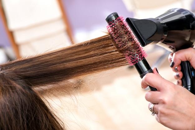 長い茶色の髪を乾かす美容院ブロー