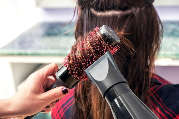 ヘアスタイリストがヘアドライヤーで髪をブラッシング