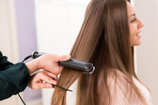 長い茶色の髪に平らな鉄を使用してヘアスタイリスト