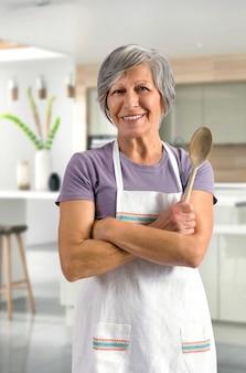 幸せなフレンドリーな年配の女性が台所で焼く
