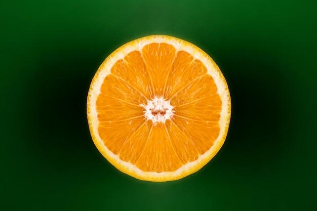 Апельсин разрезать пополам на зеленом фоне