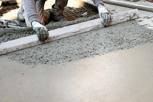 コンクリートの床を平らにする労働者