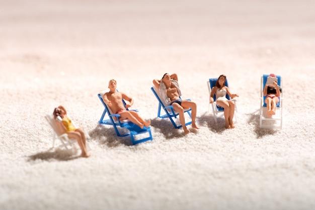 デッキチェアで日光浴のミニチュアの人々のグループ