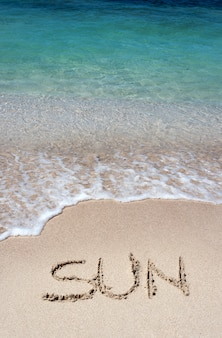 Слово солнце написано на золотом песке пляжа