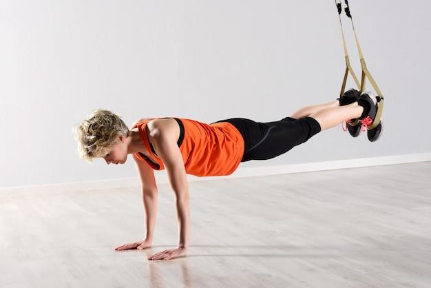 Женщина балансирует на полу с веревками вокруг ног