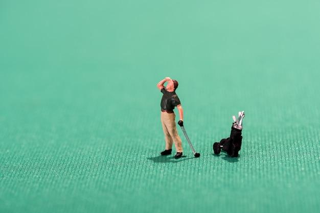 Миниатюрный гольфист, вглядываясь в даль