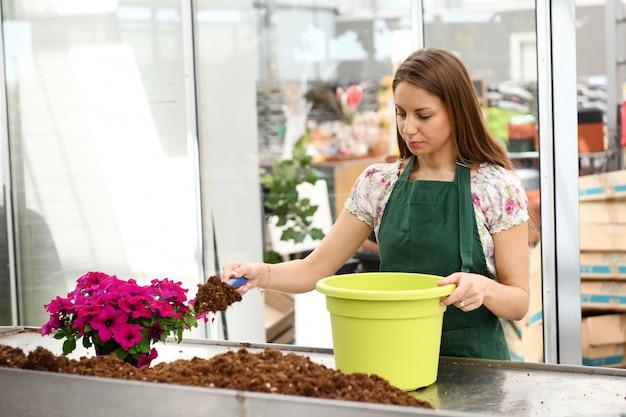 植木鉢に土をシャベルする若い女性