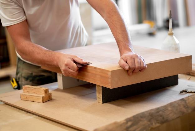 Плотник зашкурить край деревянного блока