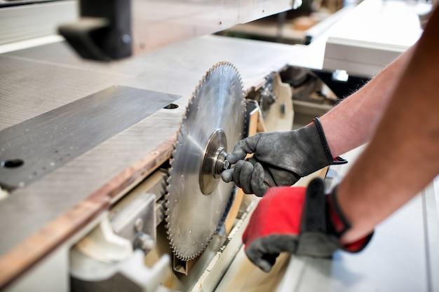 Плотник регулирует лезвие на дисковой пиле