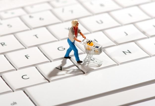 買い物客がコンピューターのキーボードでトロリーを押す