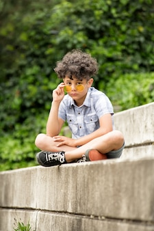 Торжественный маленький мальчик в желтых очках