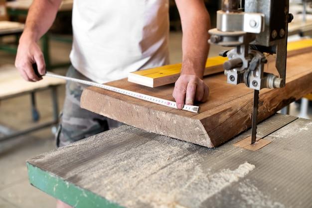 Плотник или столяр проводит измерения