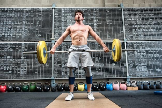 強い男が重いバーベルを持ち上げる