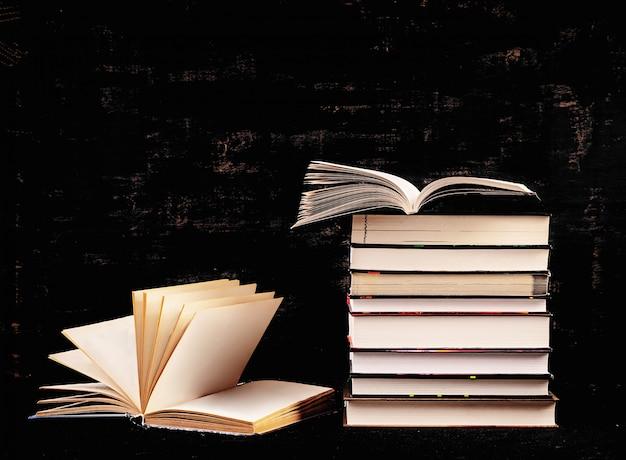 暗闇の中で異なる本のスタック。知識の概念。