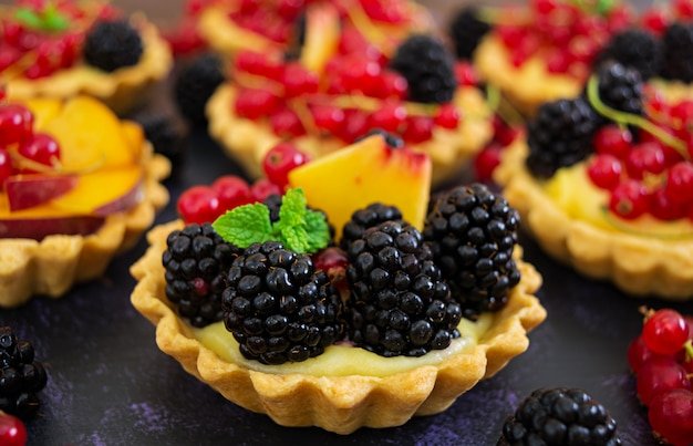 Тарталетки с разными ягодами на темной поверхности