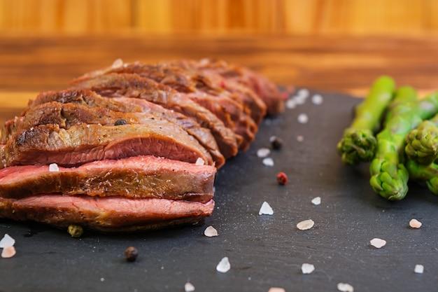 グリルしたビーフステーキと木製のアスパラガス