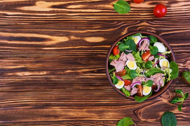 マグロ、トマト、ウズラの卵、アスパラガス、木製の玉ねぎのサラダ