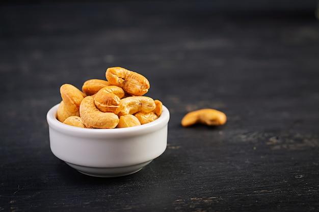 暗い背景の木にカシューナッツ。一握りのナッツ。