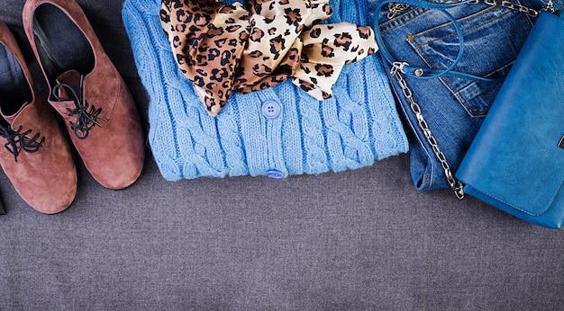 婦人服、アクセサリー、履物(青いブラウス、ジーンズ、テラコッタシューズ、バッグ)。ファッション衣装。ショッピングのコンセプト。上面図。流行の飽和色