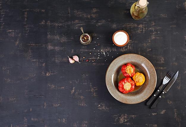 木製のテーブルにご飯とひき肉とカラフルな詰めピーマン。上面図。