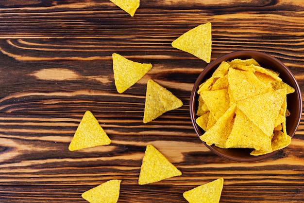 メキシコのナチョスとチーズ。木製のテーブルに分離されたコーンチップ