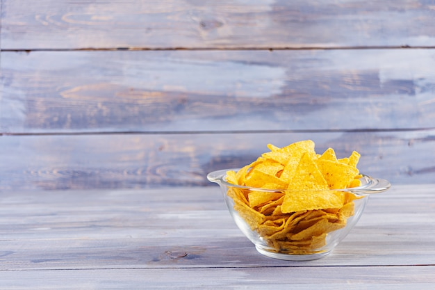 Мексиканские начос с сыром. кукурузные чипсы, изолированные на деревянный стол