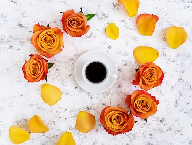 一杯のコーヒーと白のバラ