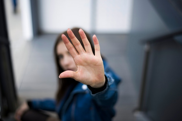 Девушка показывает знак остановки с рукой