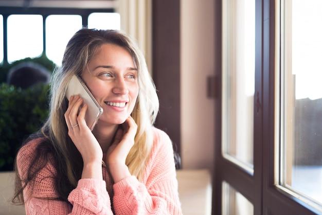 幸せな女笑顔と電話で話しています。
